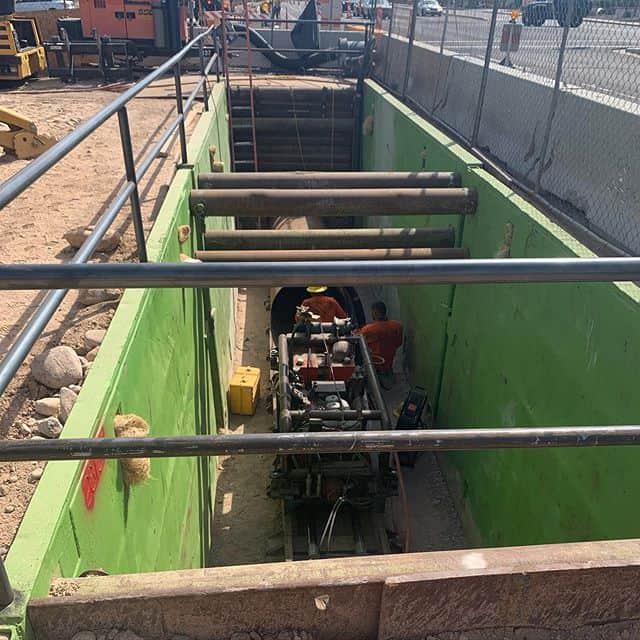 Boring job in Phoenix utilizing traditional trench boxes with plates on the end. Hand rails, and K-rail to keep your work site safe. #trenchshorerentals #treborshoringrentals #trenchshoring #trenchshields #undergroundconstruction #pipeline
